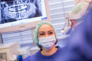 Foto einer OP-Asstentin mit Mundschutz und Haube mit Röntgenbild im Hintergrund