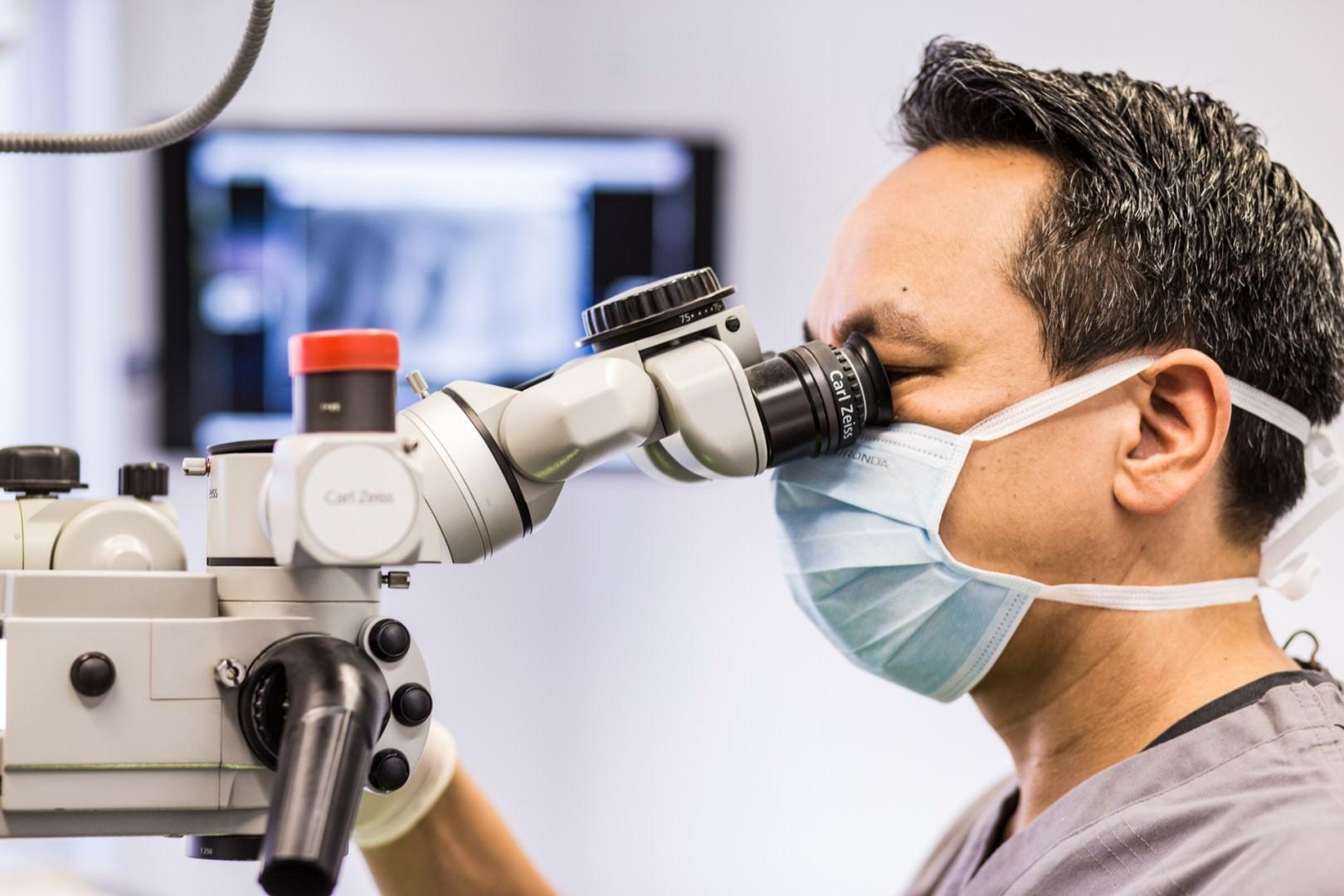 Seitliche Nahaufnahme von Dr. Marcus Pittrof mit Mundschutz am Sichtgerät