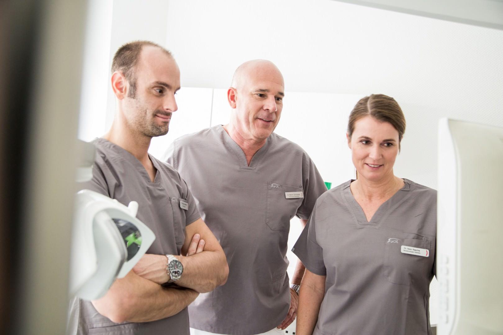 Zahnkultur Köln - Dr. Bechtold, Dr. Schneider, Frau Dr. Rasche schauen gemeinsam auf einen Bildschirm