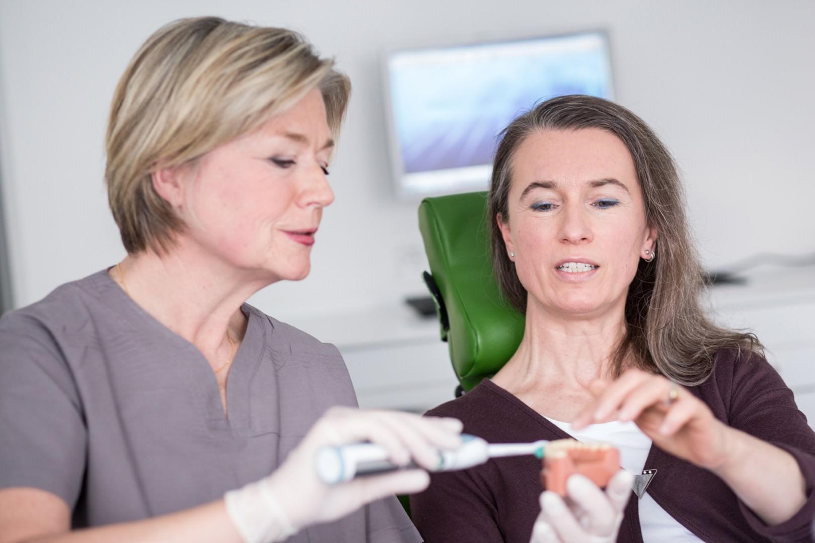 Frau Wutzke demonstriert ihrer Patientin die ideale Zahnpflege