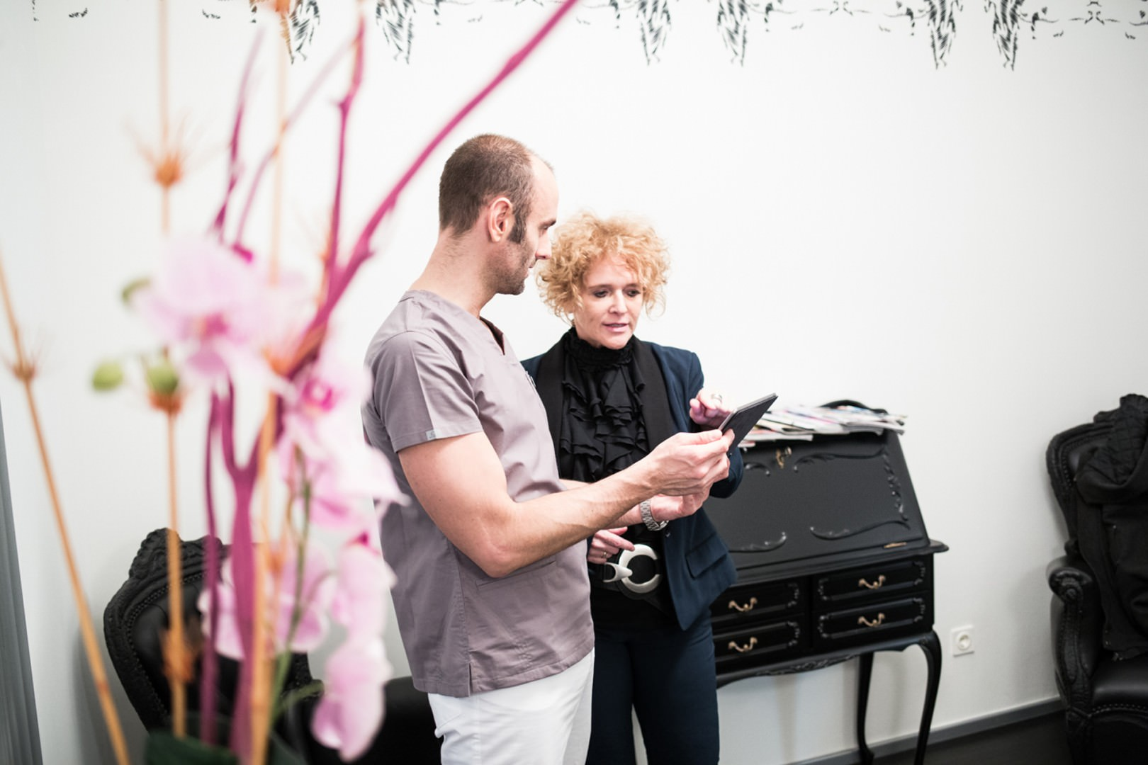 Zahnkultur Köln - Dr. Bechtold und Dagmar Spee über einem tablet in Besprechung