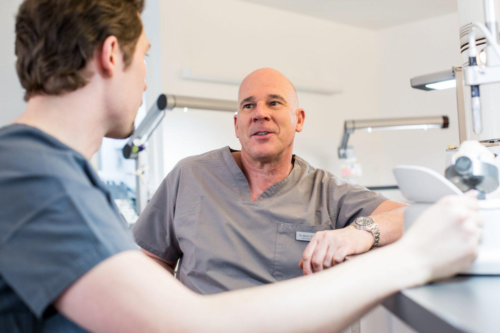 Dr. Schneider in Köln im Gespräch mit einem Zahntechniker des Praxislabors von ZAHNKULTUR)